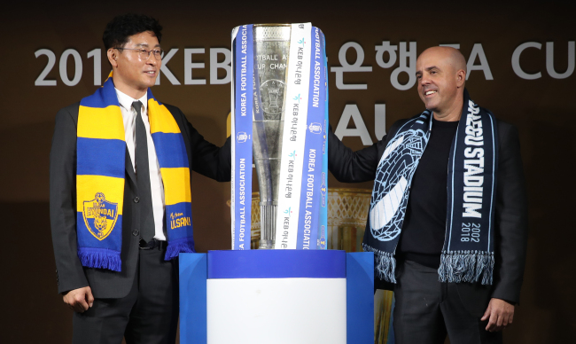 Ulsan Hyundai FC head coach Kim Do-hoon (L) and Daegu FC head coach Andre Luiz Alves Santos pose for a photo with the Korea Football Association (KFA) Cup winners` trophy at the KFA House in Seoul on Dec. 3, 2018. (Yonhap)