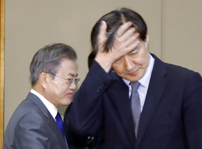President Moon Jae-in and his Senior Secretary for Civil Affairs Cho Kuk at a senior aides meeting held on Nov. 20. Yonhap