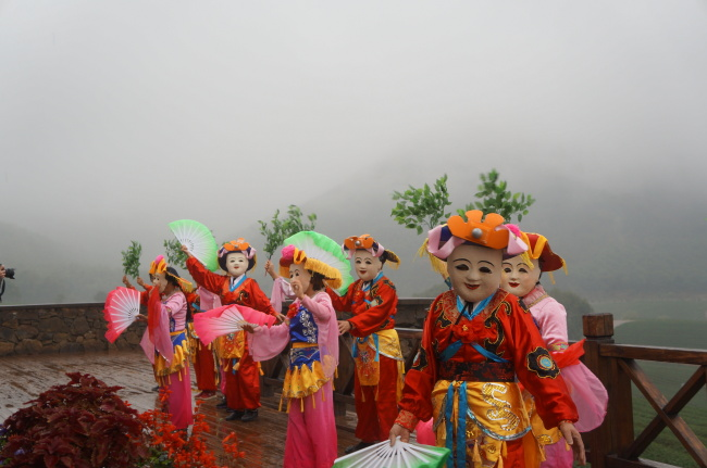 At Bamboo Sea Scenic Spot, visitors can enjoy the region's traditional masked dance. The dancers shake branches of green tea leaves to welcome guests. (Im Eun-byel/The Korea Herald)