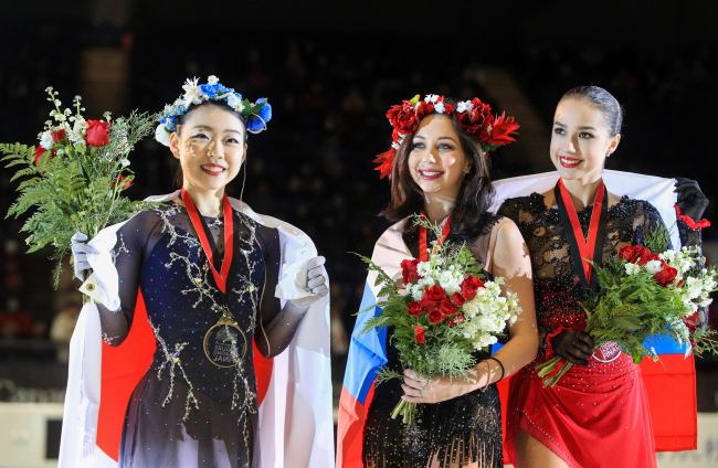 Gold medallist Rika Kihira of Japan, bronze medallist Yelizaveta Tuktamysheva of Russia, and silver medallist Alina Zagitova of Russia, from left, pose at a victory ceremony for the ladies` singles competition at the 2018/19 ISU Grand Prix of Figure Skating Final at the Doug Mitchell Thunderbird Sports Centre. (Yonhap)