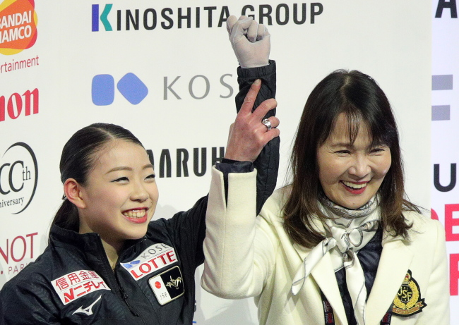 Figure skater Rika Kihira (left) of Japan with her coach Mie Hamada reacts in the kiss and cry after the ladies` free skate at the 2018/19 ISU Grand Prix of Figure Skating Final at the Doug Mitchell Thunderbird Sports Centre. (Yonhap)