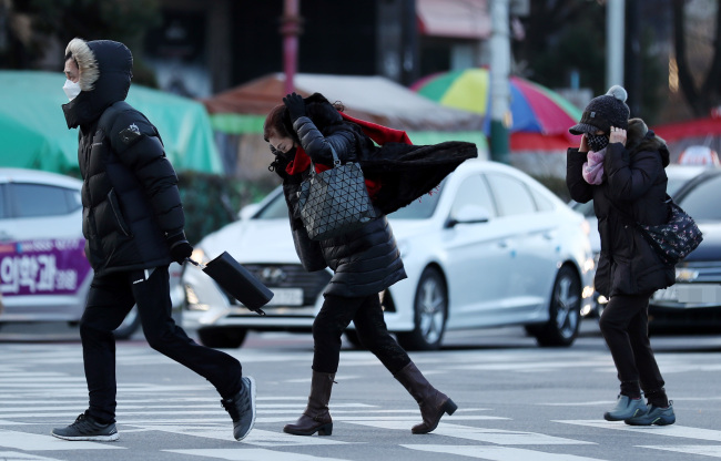 Pedestrians brace themselves in the winter cold. (Yonhap)