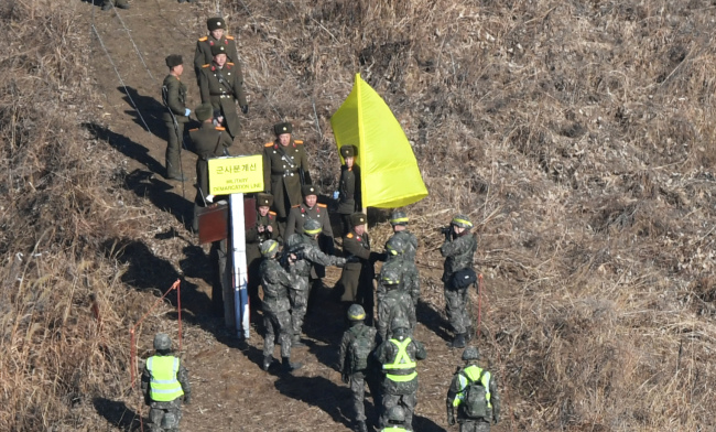 The two Koreas` military inspection teams shake hands at a cross-border region marked with a yellow flag Wednesday. Yonhap