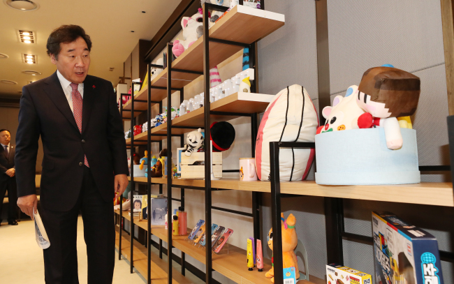 Prime Minister Lee Nak-yeon looks at products on display at a pan-governmental meeting on state affairs, held at the Sejong Government Complex on Thursday. (Yonhap)