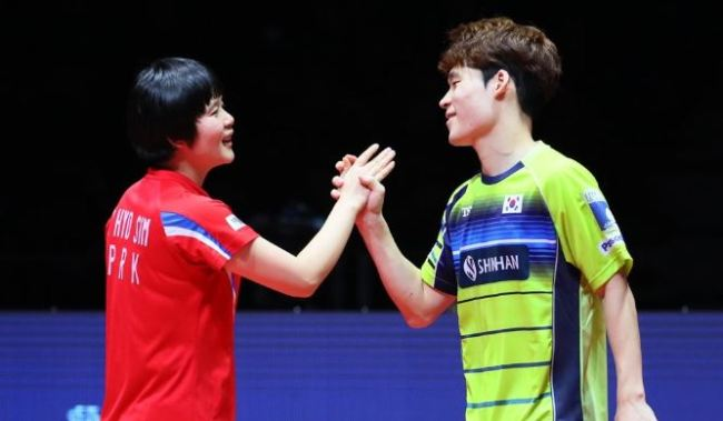 Cha Hyo-sim of North Korea (L) and Jang Woo-jin of South Korea react to their loss to Wong Chun Ting and Doo Hoi Kem of Hong Kong in the mixed doubles final at the International Table Tennis Federation World Tour Grand Finals on Dec. 15, 2018, at Namdong Gymnasium in Incheon, 40 kilometers west of Seoul. (Yonhap)
