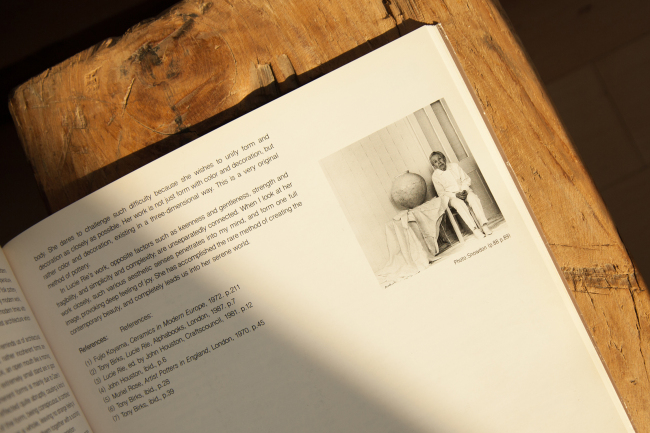 """A photograph of Lucie Rie in the book """"Issey Miyake Meets Lucie Rie"""" shows the renowned British potter sitting next to her Korean moon jar. (Courtesy of the artist)"""