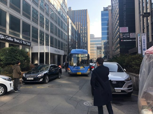 A city bus weaves through a narrow road, taking a different route due to the protest on Thursday. (Jo He-rim/The Korea Herald)
