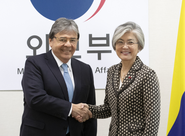 Colombian Foreign Minister Carlos Holmes Trujillo Garcia (left) poses with Korean Foreign Minister Kang Kyung-wha following a meeting in Seoul on Dec. 17. (Yonhap)
