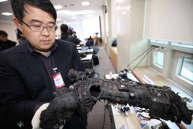 An official on the investigation team shows an EGR cooler with a hole made due to flaws in design at a press briefing at a government complex in Seoul. (Yonhap)