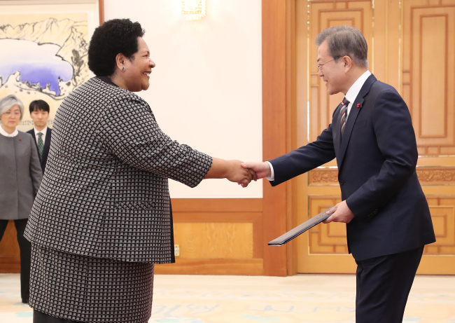 President Moon Jae-in (right) greets Ambassador Peniana Lalabalavu from Fiji, Dec. 26 (Yonhap)