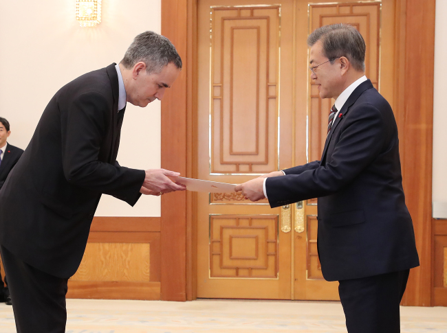 President Moon Jae-in (right) greets Ambassador Michael Danagher from Canada, Dec. 26 (Yonhap)