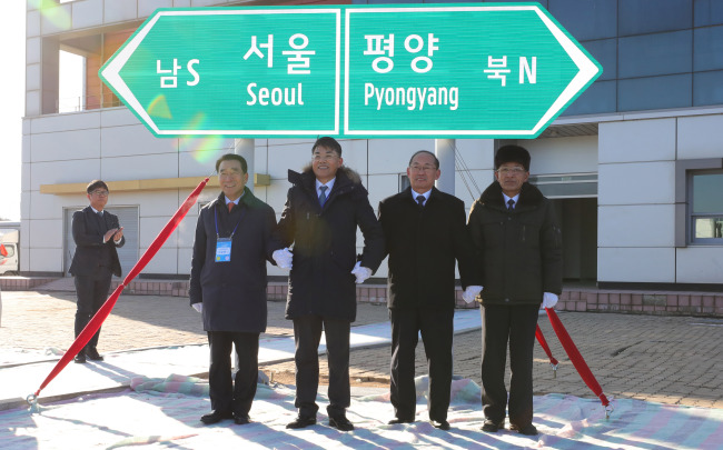 Officials unveil a signboard pointing to South Korea`s capital city of Seoul and North Korea`s Pyongyang at Panmun Station, Kaesong on Wednesday. (Joint Press Corps)