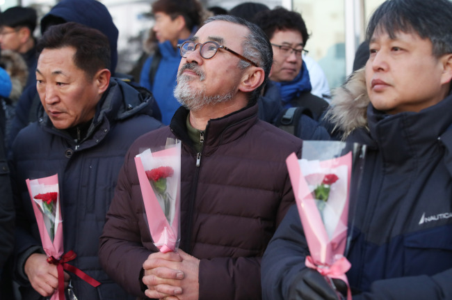 SsangYong Motor workers hold carnations at an event arranged to mark their reinstatement at the carmaker's factory in Pyeongtaek, Gyeonggi Province, Monday. (Yonhap)
