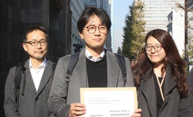 This photo, taken on Dec. 4, 2018, shows a Japanese activist and two South Korean lawyers representing the four victims of Japan`s wartime forced labor showing a document calling on Nippon Steel & Sumitomo Metal Corp. to carry out the top court`s order to compensate the victims before visiting the headquarters of the Japanese firm in Tokyo. (Yonhap)