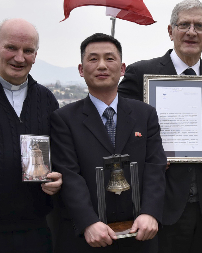 This March 20, 2018 photo made available Thursday by the Parish of Farra di Soligo, shows North Korea's acting ambassador to Italy Jo Song Gil (center) holding a model of