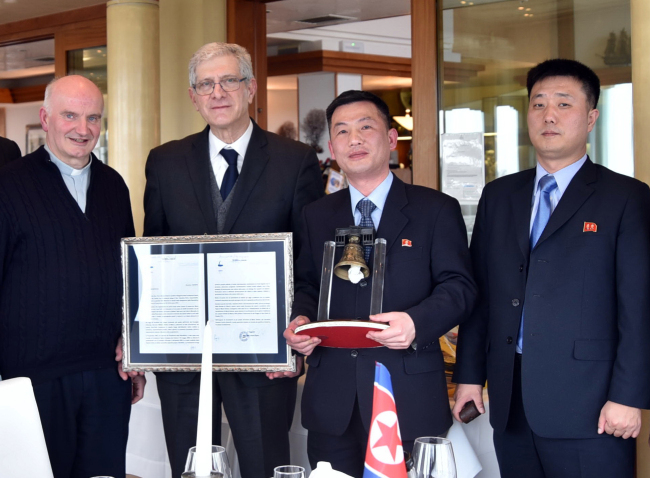 North Korea's acting Ambassador to Italy Jo Song-gil (second from right) holds a model of the Bell of Peace of Rovereto during a cultural event on the occasion of a visit by a North Korean delegation to the Veneto region in San Pietro di Feletto, near Treviso, northern Italy, in this March 20, 2018 photo released Thursday by the Parish of Farra di Soligo. Jo is flanked by Sen. Valentino Perin (second from left), don Brunone De Toffol (left), parish priest of Farra di Soligo, and North Korean Embassy official Pak Myong-gil (right). (AP-Yonhap)
