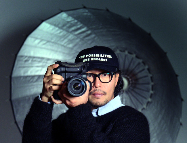 Fashion photographer Hong Jang-hyun poses with his camera for a photo shoot before an interview with The Korea Herald at Yong Jang Kwan Studio in Nonhyeon-dong, southern Seoul, on Dec. 26, 2018. (Park Hyun-koo/The Korea Herald)