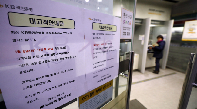 A notice is posted at an offline branch of KB Kookmin Bank on Monday, warning customers of a possible general strike slated for the following day. (Yonhap)