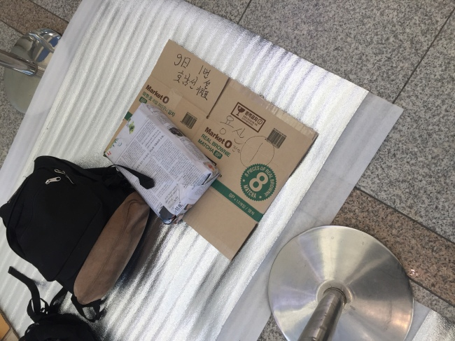 Backpacks and cardboard boxes mark the seats for those seeking tickets set aside for Wednesday's offline quota. (Park Ju-young / The Korea Herald)