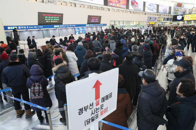 People wait in a line to get train tickets for the Lunar New Year holiday on Tuesday morning at Seoul Station (Yonhap)