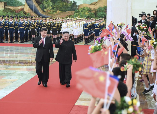 In this June 19, 2018, file photo provided by China's Xinhua News Agency, Chinese President Xi Jinping(left) and North Korean leader Kim Jong-un, (right) walk together during a welcome ceremony for Kim at the Great Hall of the People in Beijing. (AP-Yonhap)