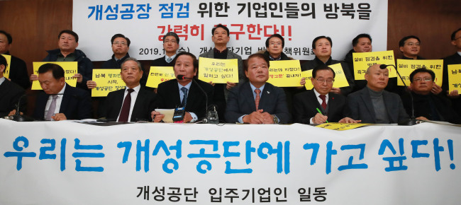 Members of a committee of business owners, who operated in Kaesong industrial complex, hold placard reading,