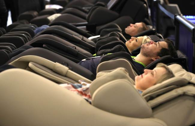 Attendees sit in Positive Posture massage chairs during CES 2019 at the Sands Expo and Convention Center on Tuesday in Las Vegas, Nevada. (AFP-Yonhap)