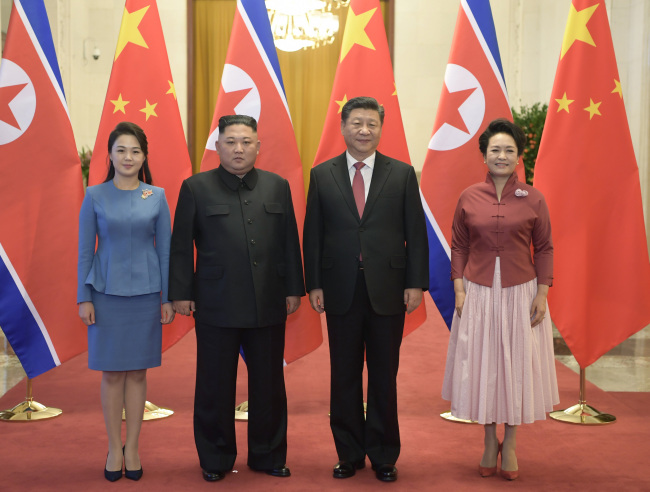 Chinese leader Xi Jinping and his wife Peng Liyuan pose for photos with NK leader Kim Jong-un and his wife Ri Sol-ju in Beijing on Wednesday. (Xinhua-Yonhap)