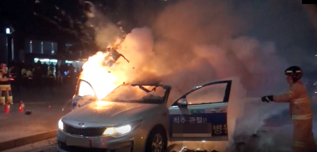 Fire fighters put off a taxi on fire after taxi driver Lim, 65, lit himself on fire on Wednesday evening in opposition to Kakao carpool service in front of Gwanghwamun Station. (Yonhap)