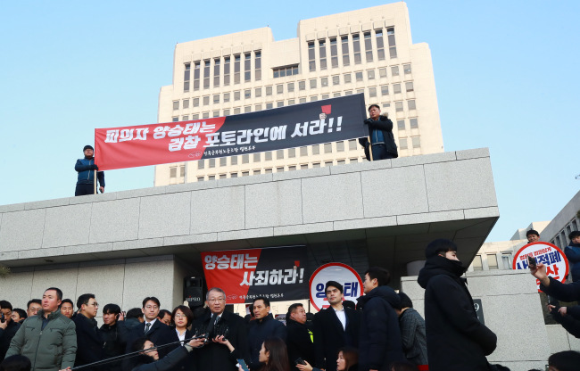 """The Korean Government Employees' Union hold a rally at the front gate of the Seoul Central District Prosecutors' Office with a placard that read """"Stand before the court not the prosecution!"""" (Yonhap)"""