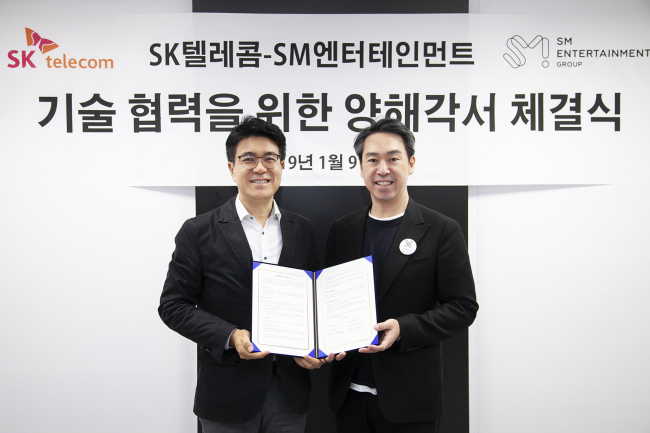 SKT chief technology officer Park Jin-hyo(left) and S.M. Entertainment CEO Kim Youg-min. SK Telecom