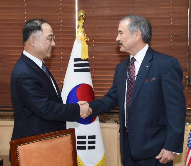 Hong Nam-ki (L), the minister of economy and finance, shakes hands with US Ambassador to South Korea Harry Harris ahead of their talks at the government complex building across from the US Embassy in central Seoul on Jan. 11, 2019. This photo was provided by the Ministry of Economy and Finance. (Yonhap)
