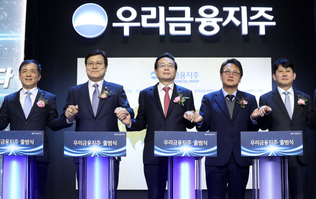 Sohn Tae-seung (third from left), chairman of Woori Financial Holdings and Woori Bank, poses at a ceremony to mark the bank's official transformation into a financial holding company at the Woori Bank headquarters in central Seoul, Monday. From left: Korea Deposit Insurance Corp. CEO Wi Seong-bak; Financial Services Commission Chairman Choi Jong-ku; Woori Financial Holdings Chairman Sohn; Rep. Min Byung-doo of the ruling Democratic Party of Korea; and Yoo Kwang-yeol, first senior deputy governor of the Financial Supervisory Service. (Yonhap)