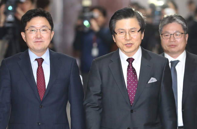 Former prime minister Hwang Hyo-ahn (center) walks to a press conference after announcing his Liberty Korea Party membership on Tuesday. (Yonhap)
