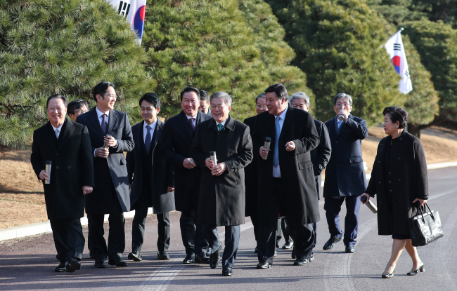 Business leaders and aides accompany President Moon Jae-in (center) on a walk around the garden at Cheong Wa Dae on Tuesday. Yonhap
