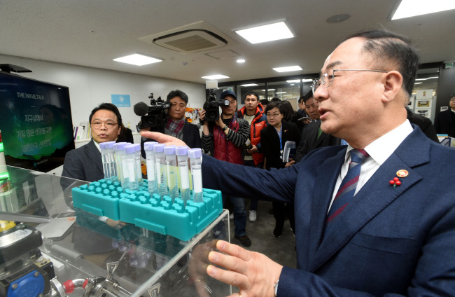 Finance Minister Hong Nam-ki is briefed on the business portfolio of a startup stationed at a local incubator for budding enterprises in Yangjae, southern Seoul, Wednesday. Yonhap