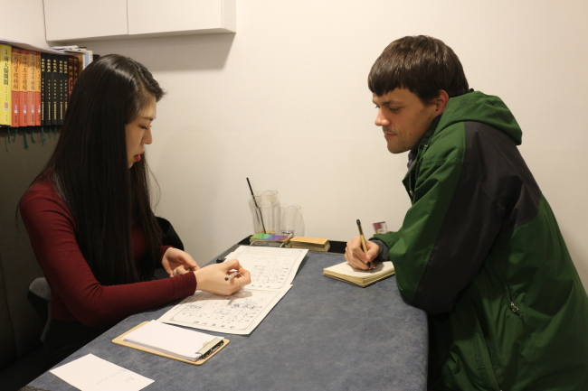 Saju fortuneteller Hyo-ri (left) gives a reading to The Korea Herald's Kevin Lee Selzer. (Lim Jeong-yeo/The Korea Herald)