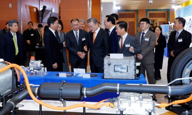 President Moon Jae-in (center) looks at a model of the hydrogen fuel cell electric vehicle Nexo during a visit to a Hyundai Motor facility in Ulsan on Thursday. (Yonhap)