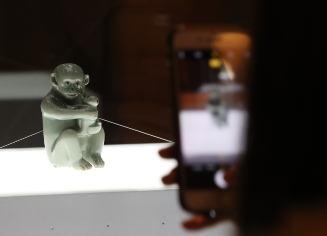 "A visitor takes a photo of National Treasure No. 270 ""Celadon Wine Pot in the Shape of Monkey Figure"" at the ""A Collection for Korea"" exhibition held at the Dongdaemun Design Plaza in Seoul on Jan. 3. / Yonhap"