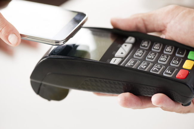 A person pays using a smartphone equipped with NFC technology (123RF)