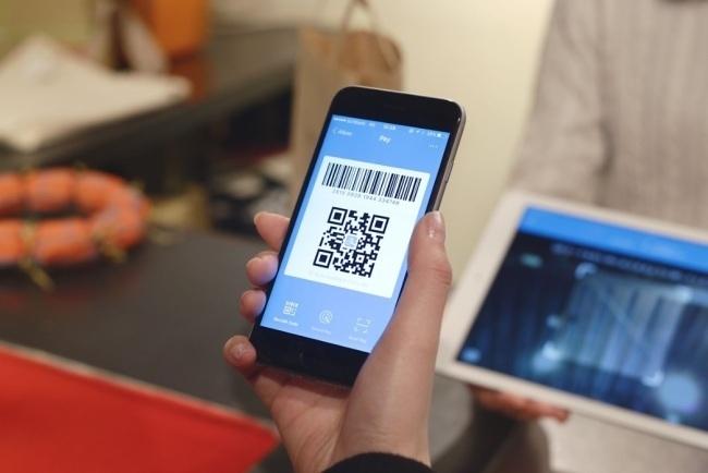 A smartphone screen shows a QR code (Herald DB)