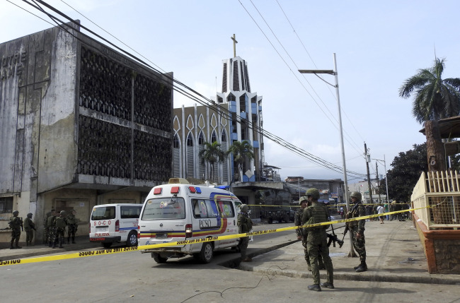 Police investigators and soldiers attend the scene after two bombs exploded outside a Roman Catholic cathedral in Jolo, the capital of Sulu province in southern Philippines, Sunday. AP