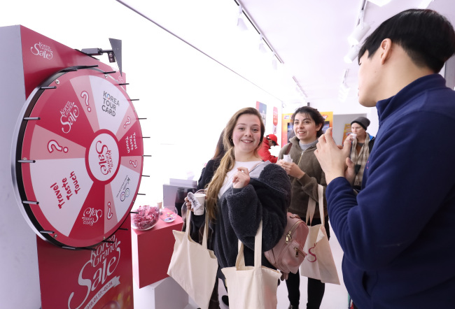 A visitor participates in an event at the welcome center of the Korea Grand Sale located at Cheonggye Plaza in Jongno, central Seoul, in this undated handout photo. (Visit Korea Committee)