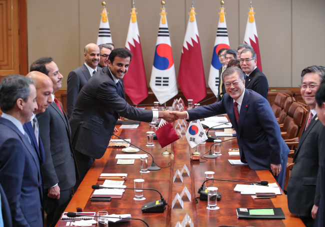 President Moon Jae-in (right) shakes hands with Sheikh Tamim bin Hamad Al Thani, the emir of Qatar, ahead of their summit at Cheong Wa Dae in Seoul on Monday (Yonhap)