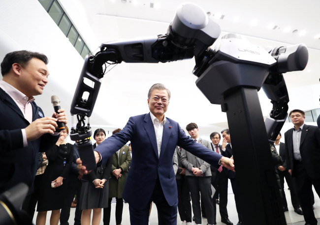 President Moon Jae-in tries operating the arms of a robot built by Naver Labs, which can lift more than 100 kilograms, at Dongdaemun Design Plaza in central Seoul on Tuesday. (Yonhap)