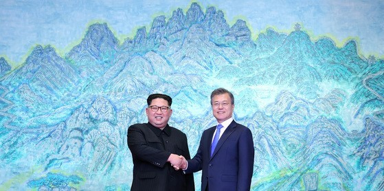 """North Korean leader Kim Jong-un and South Korean President Moon Jae-in shake hands in front of Min Joun-ki's landscape painting """"Mount Bukhan"""" in the Peach House at Panmunjom during the inter-Korean summit in April 2018. (Joint Press Corps)"""