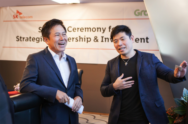 SKT CEO Park Jung-ho (left) talks with Grab co-founder Anthony Tan at the company's headquarters in Seoul on Wednesday. (SK Telecom)