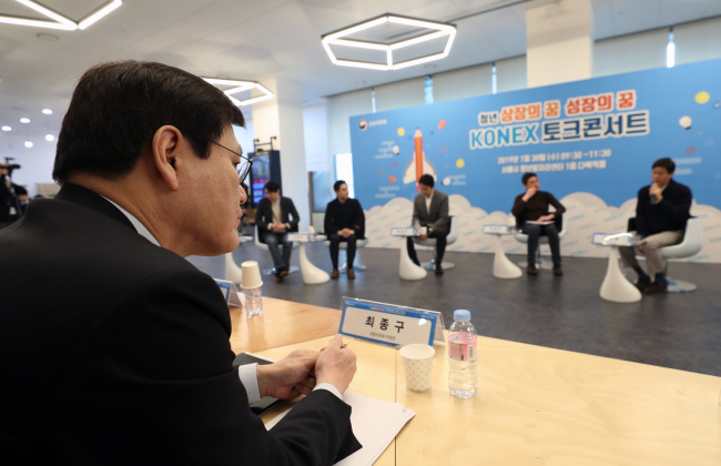 Financial Services Commission Chairman Choi Jong-ku watches a debate on vitalizing the Konex market at an event held in central Seoul on Wednesday. (Yonhap)