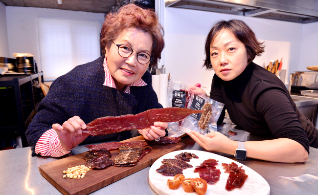 Ban Ga Won CEO Kim Jung-ja and her daughter Kim Ji-yoon pose with Jung Yook Po beef jerky products at the brand's cooking studio in Eunpyeong-gu, western Seoul. The beef jerky is made with quality beef from Pyeongchang, marinated with soy sauce and dried naturally at the city in Gangwon Province. (Park Hyun-koo / The Korea Herald)