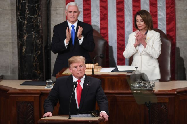 US President Donald Trump, flanked by speaker of the US House of Representatives Nancy Pelosi and US Vice President Mike Pence, takes the podium to deliver the State of the Union address at the US Capitol in Washington, DC, on February 5, 2019. (Photo by SAUL LOEB / AFP)